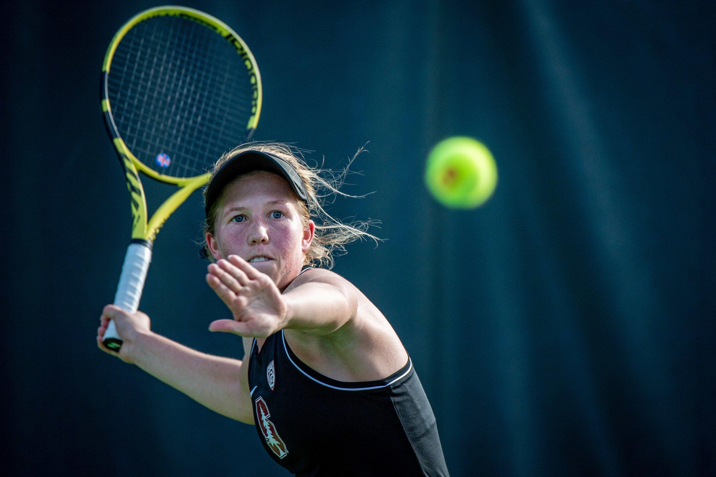 Senior Emily Arbuthnott prepares to swing at an incoming tennis ball.