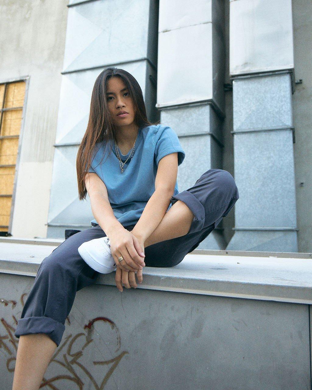 Emily Vu sits on a ledge in an urban environment.