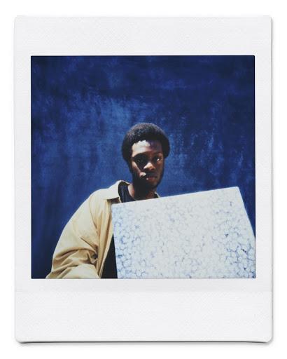 Osadolor Osawemwenze holding a piece of artwork