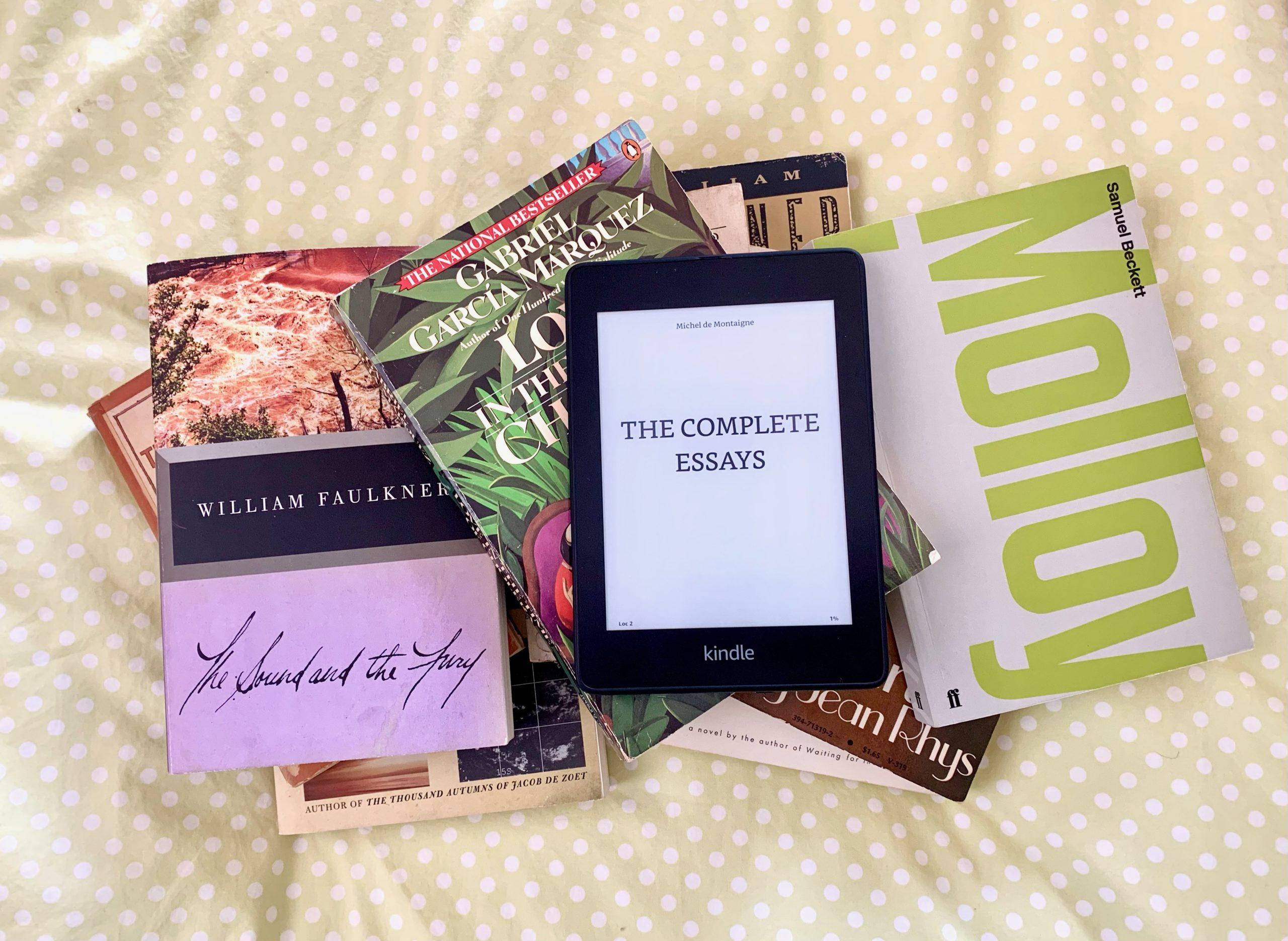 "Kindle version of Michel de Montaigne's ""Essays"" on top of a pile of books"