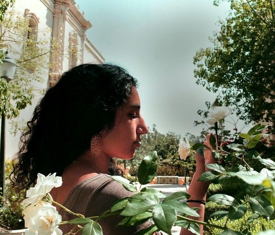 poet Maya Salameh '22 in profile, in some foliage