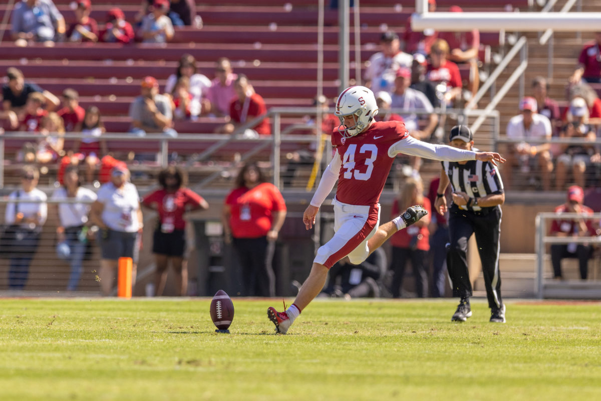 Sophomore kicker Joshua Karty extends his leg back to kick a football on the field.