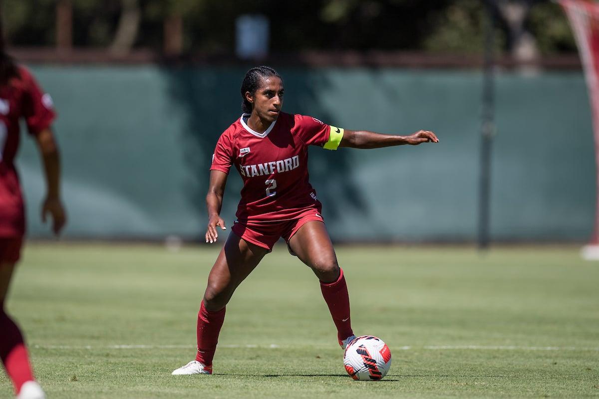 Senior defender Naomi Girma dribbles a soccer ball down a soccer field.